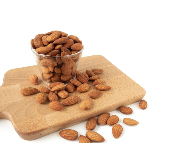 Organic almonds in glass bowl with wood cutting board and heap almonds isolated on white