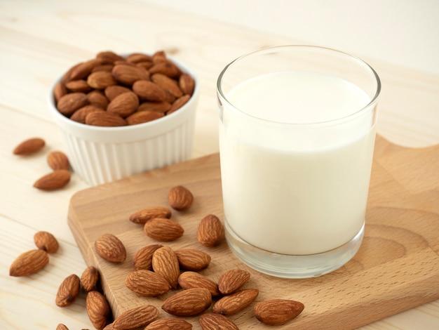 Органическое миндальное молоко в стакане и куча миндальных орехов на деревянной разделочной доске и миндаль
