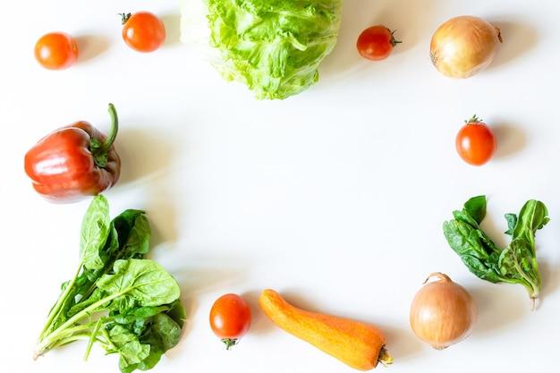 유기농 및 바이오 신선한 야채는 흰색 테이블 배경의 프레임에 있습니다. 건강한 자연 익은 채식 야채 개념입니다. 샐러드 재료, 농산물 직판장