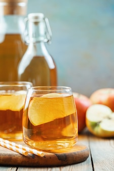 Organic apple cider or juice on a wooden table with copy space. two glasses with drink and autumn leaves on rustic background.