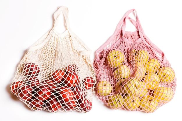 白い背景、エコショッピングバッグのコンセプトで買い物をするための籐の袋の有機リンゴ。コピースペースを備えたゼロウェイストコンセプト、プラスチックフリーコンセプト