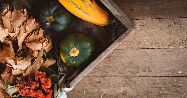 신선한 야채와 잎의 유기농 가을 장식 수확은 보드 배경에 있는 오래된 나무 상자에 있습니다. 여유 공간, 평면도.