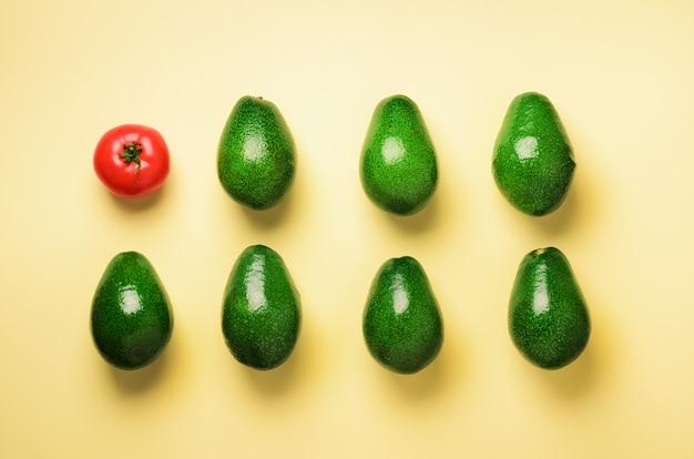 유기농 아보카도, 파란색과 노란색 배경에 토마토. 최소한의 평평한 평신도 스타일의 야채 패턴.