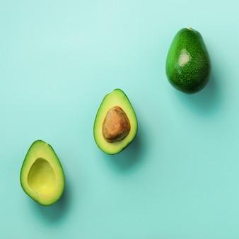 씨앗, 아보카도 반쪽 및 파란색 배경에 전체 과일 유기농 아보카도. 최소한의 평평한 레이 스타일의 녹색 아보카도 패턴.