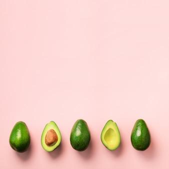 씨앗, 아보카도 반쪽 및 분홍색 배경에 전체 과일 유기농 아보카도. 최소한의 평평한 레이 스타일의 녹색 아보카도 패턴.