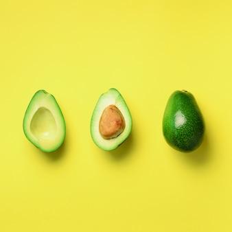 씨앗, 아보카도 반쪽과 노란색 배경에 전체 과일 유기농 아보카도. 최소한의 평평한 레이 스타일의 녹색 아보카도 패턴.