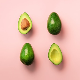 Organic avocado with seed, avocado halves and whole fruits on pink background. green avocadoes pattern in minimal flat lay style.
