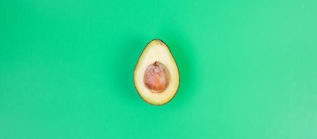Органический авокадо с семенами на зеленом фоне