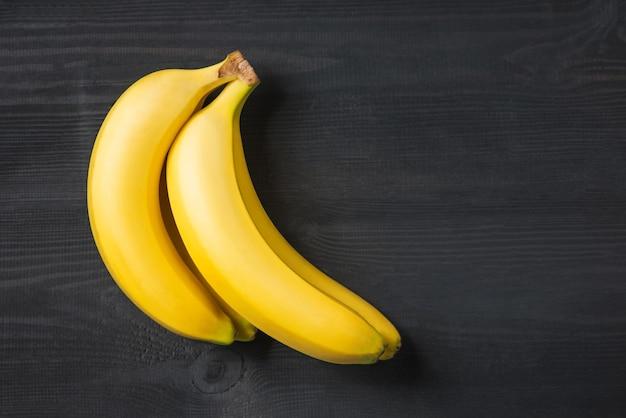 黄色の背景の上の有機バナナ健康的な果物