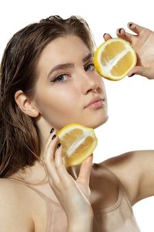 Органические красивая молодая женщина с ломтиком лимона на белом фоне косметика и естественный макияж