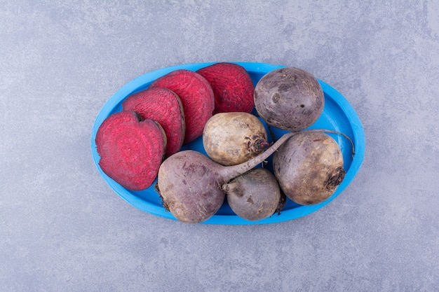 Organic beetroots on a blue platter concrete background.