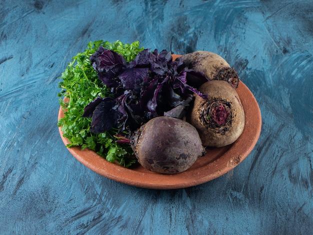 Barbabietole organiche, aneto e foglie di basilico su piatto in ceramica.