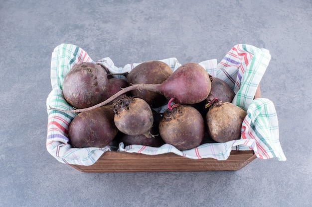 Organic beetroots on a wooden platter isolated on grey concrete background.