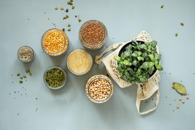 ゼロウェイストショップのオーガニックバイオバルク製品。廃棄物の少ないライフスタイルでのキッチンでの食品保管。テーブルの上のガラスの瓶の中の穀物と穀物。プラスチックのない食料品店での環境にやさしい買い物。