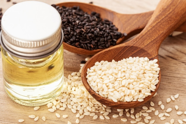Organic black and white sesame seeds in wooden spoon with oil bottle