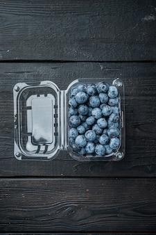 プラスチックの箱のパッケージの有機ブルーベリー、黒い木製のテーブルの背景、上面図フラットレイ