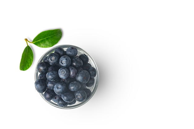 Organic blueberries in transparent bowl isolated on white background with leaf