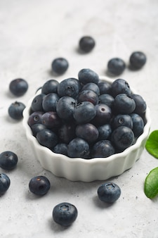 Organic blueberries in a white bowl on a concrete background with a leaf