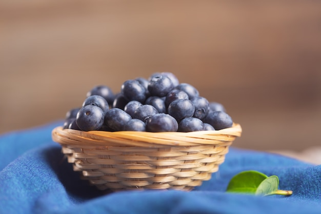 Organic blueberries in a wicker bowl on a napkin with a leaf