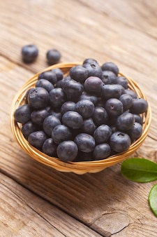 Organic blueberries in a wicker bowl with leaves