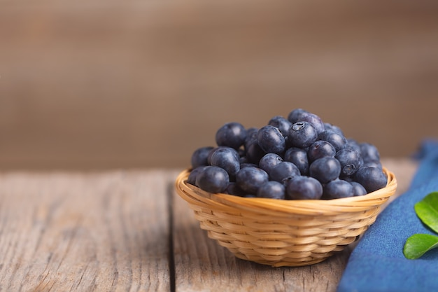 Organic blueberries in wicker bowl on wooden background with blue napkin and leaf. selective focus