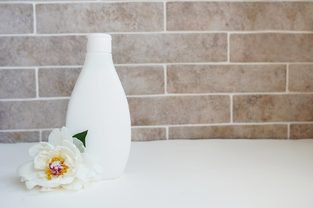 Organic body lotion and fresh white flower in bath
