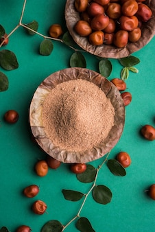 Organic borkut powder of indian jujube ber or berry or ziziphus mauritiana, which is a type of date. over moody background, selective focus