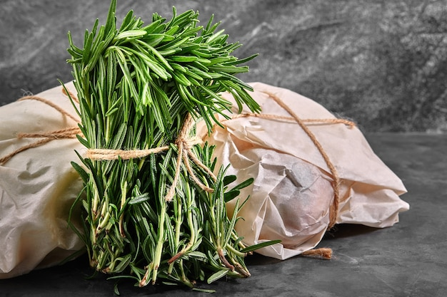 Органический букет из свежего розмарина на сером фоне. красиво связанный пучок свежей травы. доставка продукции, копии места.