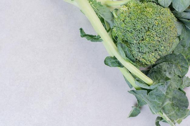 Broccoli organici con foglie sul tavolo bianco.