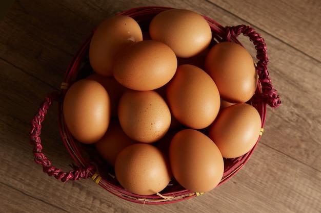 나무 배경, 평면도에 바구니에 유기농 갈색 계란.