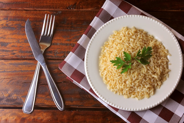 Organic brown rice grain cooked in white dish on rustic wooden table