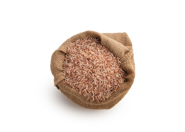 Organic brown rice in sack on white isolated