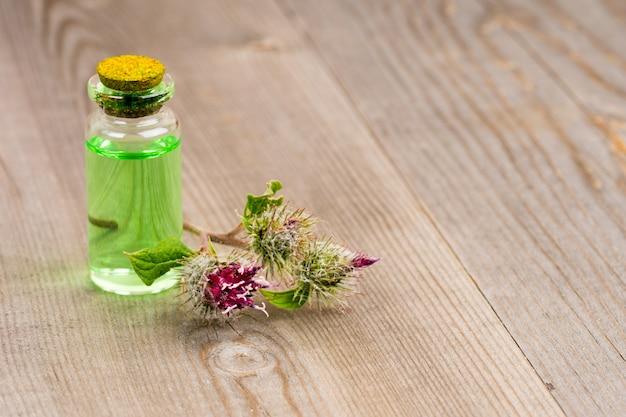 Органическое репейное масло в стеклянной бутылке и цветы лопуха