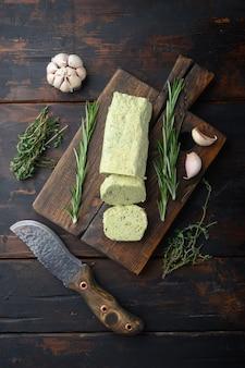Органическое масло с травами для бутербродов и стейков на старом темном деревянном столе