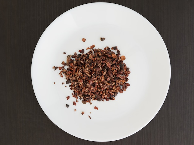 Organic cacao nibs on a white plate. top view.
