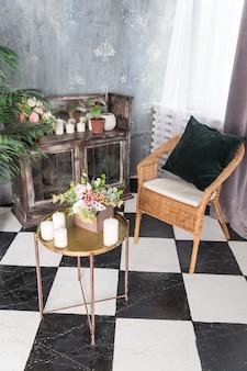 有機キャンドルと小さなテーブルの上に花のついた木箱。ロフトのインテリア、ミニマリズムのコンセプト。