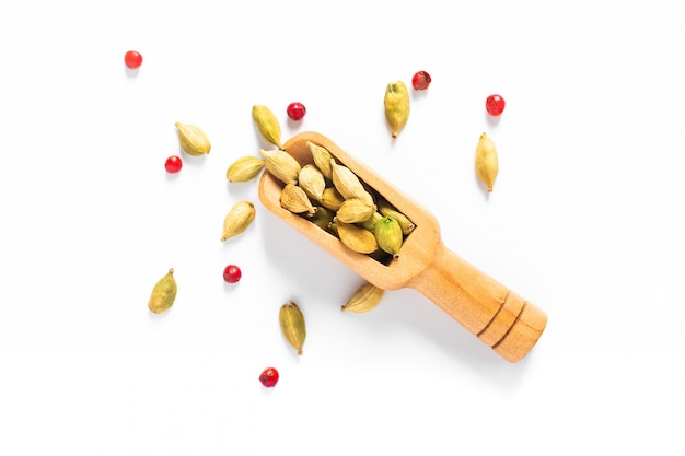 Organic cardamom and pink peppercorn pods in bamboo scoop on white background