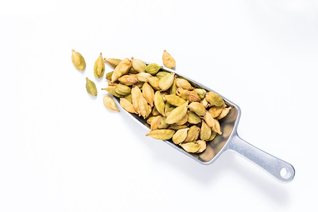 Organic cardamom pods in iron scoop on white background