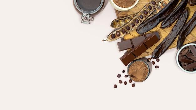 베이지색 배경 메뚜기 콩 건강 식품에 유기농 캐롭 포드 분말과 캐롭 당밀