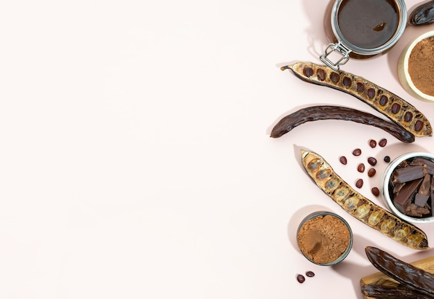 Organic carob pods, powder and carob molasses on a beige background, locust bean healthy food, ceratonia siliqua harnup. natural vegan eating. creative food background. copy space. flat lay.top view