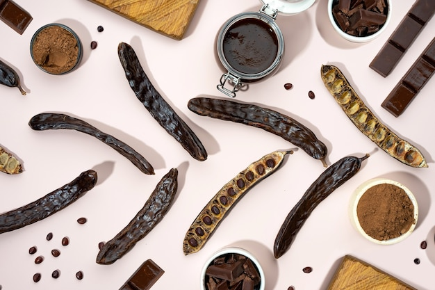 Organic carob pods, powder and carob molasses on a beige background, locust bean healthy food, ceratonia siliqua harnup. natural vegan eating. creative food pattrern. flat lay. top view