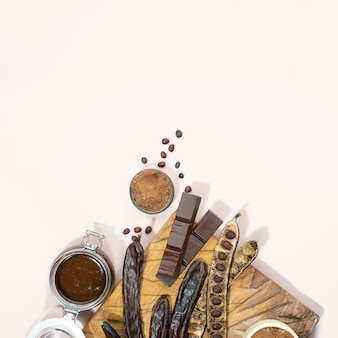 Organic carob pods, powder and carob molasses on a wooden board, beige background, locust bean healthy food, ceratonia siliqua harnup. natural vegan eating. creative food background. copy space.