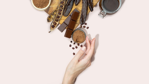 Organic carob pods, powder, chocolate and carob molasses on a wooden board in a woman hand on a pink background, locust bean healthy food, natural vegan eating. creative food background. copy space.
