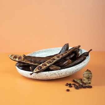 Organic carob pods, seeds in a ceramic plate on a beige background, locust bean healthy food, ceratonia siliqua harnup. natural vegan eating. creative food background. copy space. square.