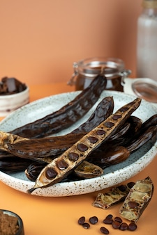 Organic carob pods, seeds in a ceramic plate on a beige background, locust bean healthy food, ceratonia siliqua harnup. natural vegan eating. creative food background. copy space. top view