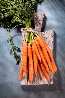 Organic carrot on wood cutting board, closeup photo