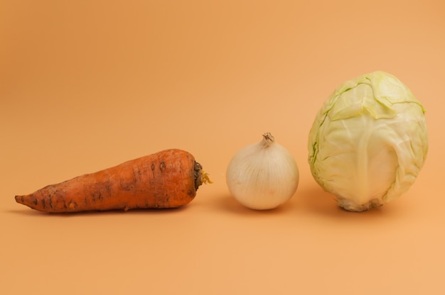 Organic carrots,onions and cabbage on beige background.