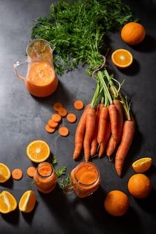 有機にんじんオレンジと天然ジュースの水差しとにんじんジュースのグラス2杯