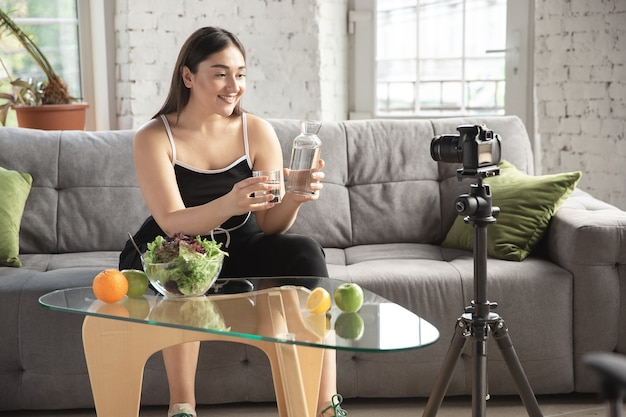 Organic. caucasian blogger, woman make vlog how to diet and lost weight, be body positive, healthy eating. using camera recording her fruits salad preparing. lifestyle influencer, wellness concept.