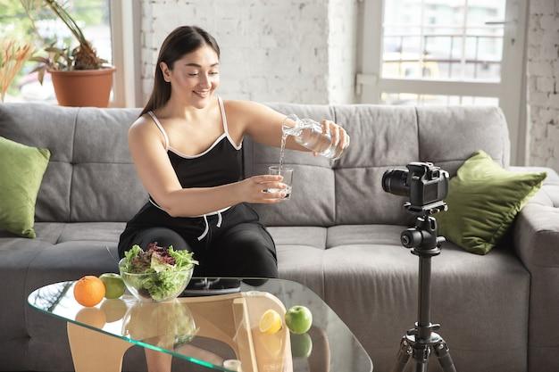 본질적인. 백인 블로거, 여성은 다이어트와 체중 감량 방법을 vlog로 만들고 몸에 긍정적이고 건강한 식생활을 합니다. 카메라를 사용하여 그녀의 과일 샐러드 준비를 녹화합니다. 라이프 스타일 인플루언서, 웰빙 개념.